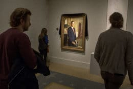 Visitors stop to look at the official portrait of former President George H.W. Bush as it is draped in black cloth at the National Portrait Gallery in Washington, Monday, Dec. 3, 2018, to mark his passing. Bush will lay in state at the Capitol building this week before being buried in Texas. (AP Photo/Andrew Harnik)