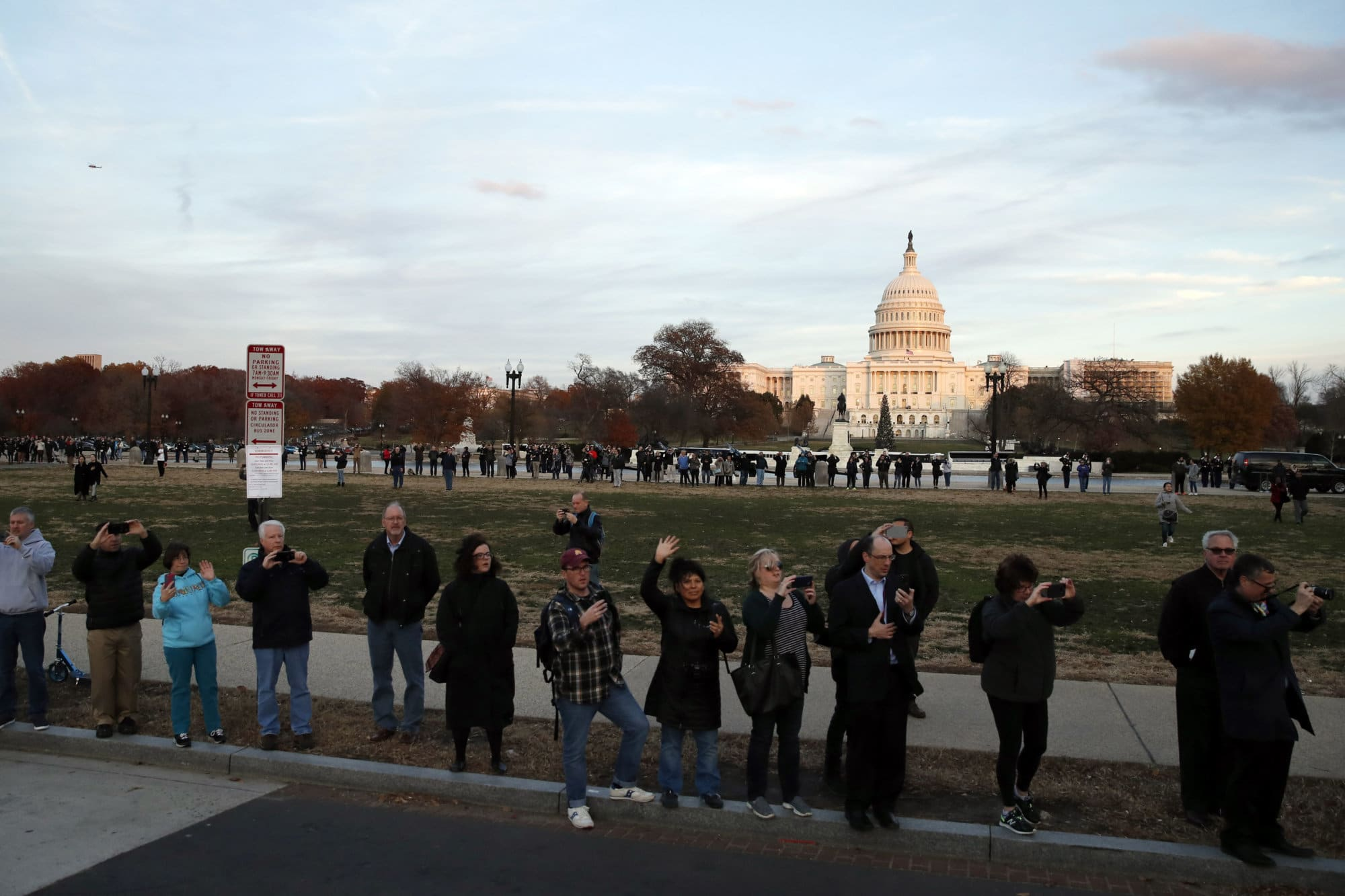People watch as the hearse carrying the remains of former President George H.W. Bush passes by the West Front of the U.S. Capitol, Monday, Dec. 3, 2018, in Washington.(AP Photo/Alex Brandon, Pool)