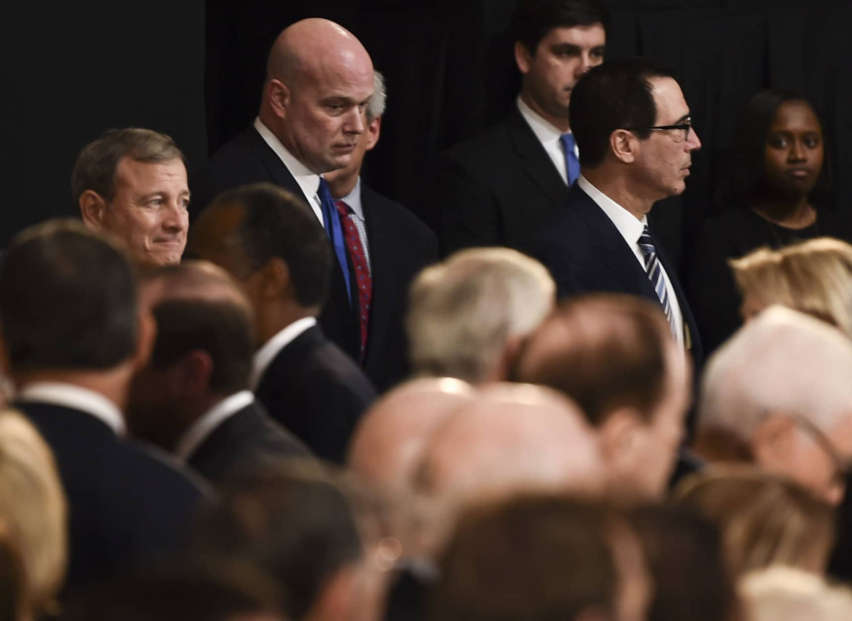 Member of the Supreme Court Chief Justice, John Roberts, left, acting Attorney General, Matthew Whitaker, center, and Secretary of the Treasury, Steven Mnuchin, right, wait for the casket containing the remains of former President George H.W. Bush to arrive at the Capitol in Washington, Monday, Dec. 3, 2018. (Brendan Smialowski/Pool Photo via AP)