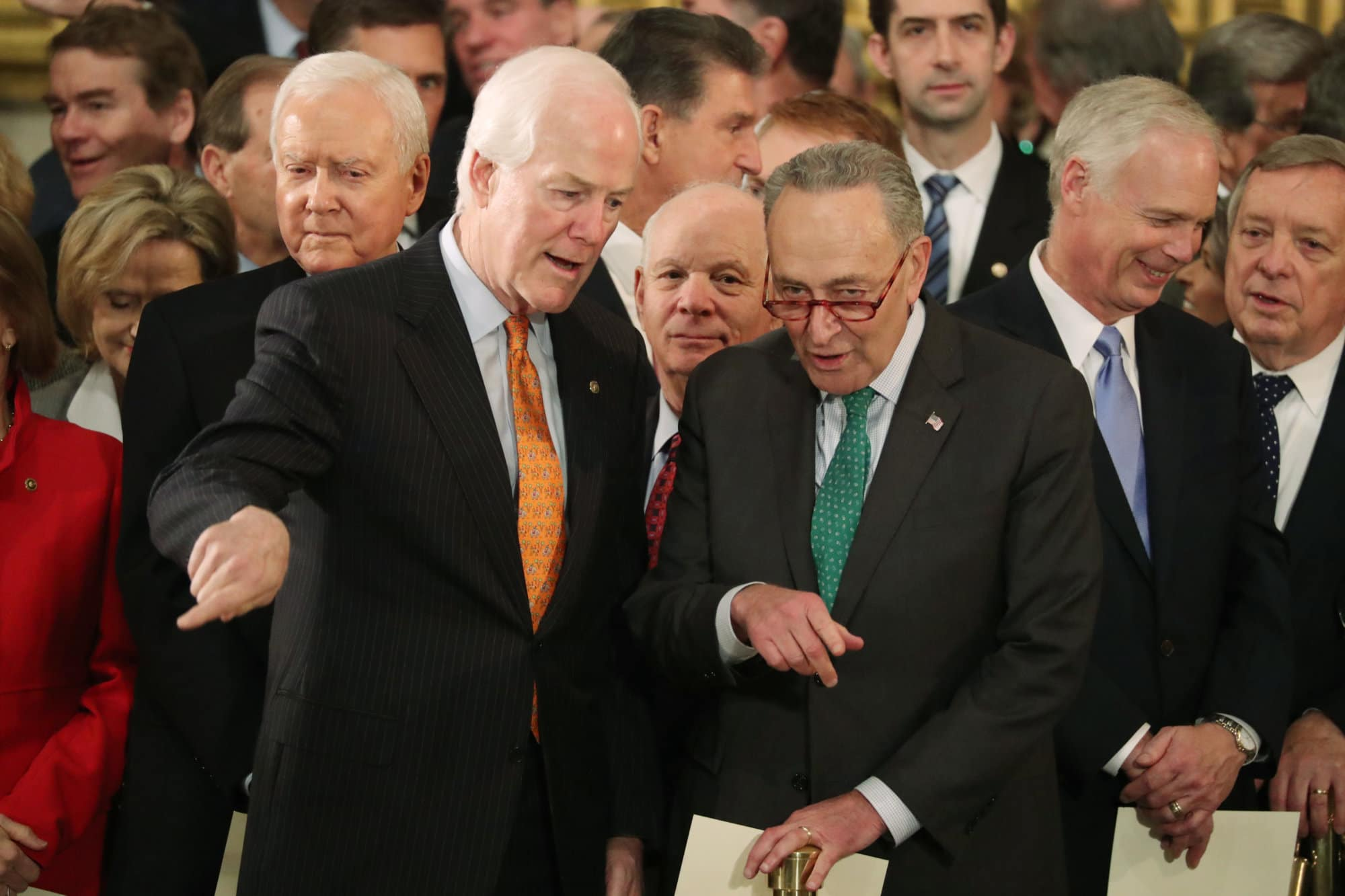 U.S. Senate Majority Whip John Cornyn and Senate Minority Leader Chuck Schumer talk while Sen. Orrin Hatch, back left, looks on as they attend ceremonies for former President George H.W. Bush at the Capitol in Washington, Monday, Dec. 3, 2018. (Jonathan Ernst/Pool Photo via AP)