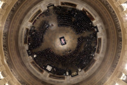 The flag-draped casket of former President George H.W. Bush is placed by a joint services military honor guard into the U.S. Capitol Rotunda Monday, Dec. 3, 2018, in Washington. (Pool photo by Morry Gash via AP)