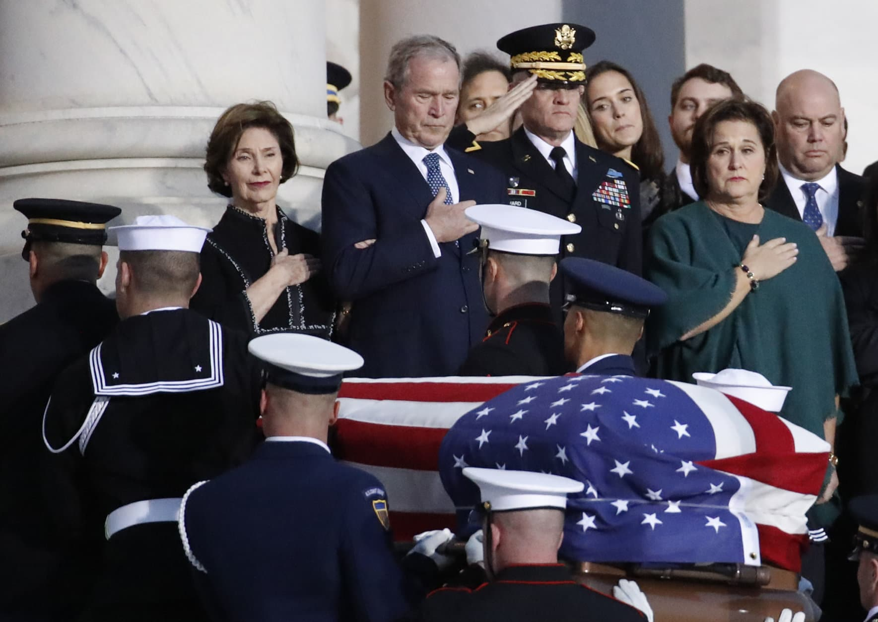 Former President George W. Bush and other family members watch as the flag-draped of former President George H.W. Bush is carried by a joint services military honor guard to lie in state in the rotunda of the U.S. Capitol, Monday, Dec. 3, 2018, in Washington.(AP Photo/Alex Brandon, Pool)