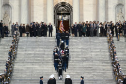 Family members and others watch as the flag-draped of former President George H.W. Bush is carried by a joint services military honor guard to lie in state in the rotunda of the U.S. Capitol, Monday, Dec. 3, 2018, in Washington. (Doug Mills/The New York Times via AP, Pool)