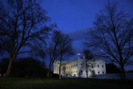 With the American flag at half-staff, dusk falls over the White House, Monday, Dec. 3, 2018, in Washington, as the state funeral for former President George H. W. Bush begins at the U.S. Capitol. (AP Photo/Jacquelyn Martin)