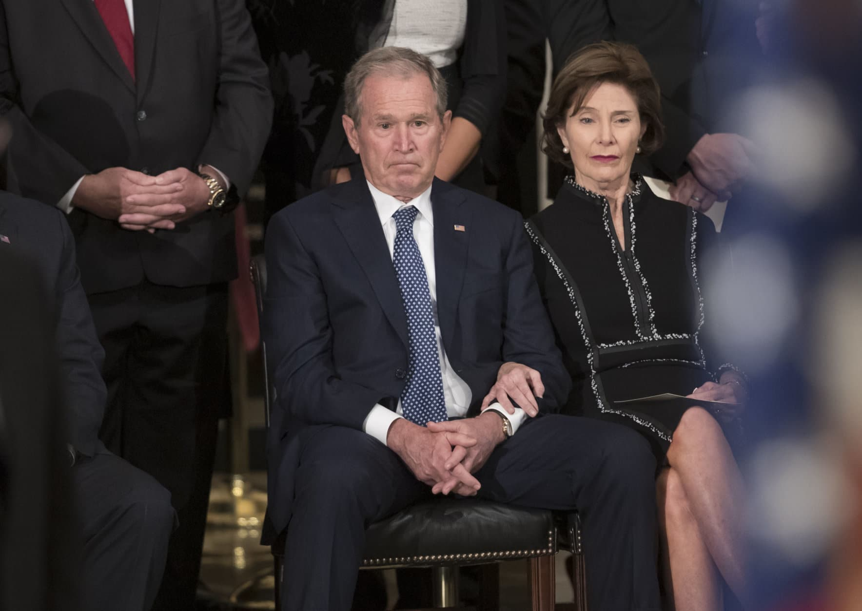 Former President George W. Bush, sits with former first lady Laura Bush, during ceremonies for his father, former President George H.W. Bush, as he lies in state at the Capitol Rotunda where in Washington, Monday, Dec. 3, 2018. (AP Photo/J. Scott Applewhite)