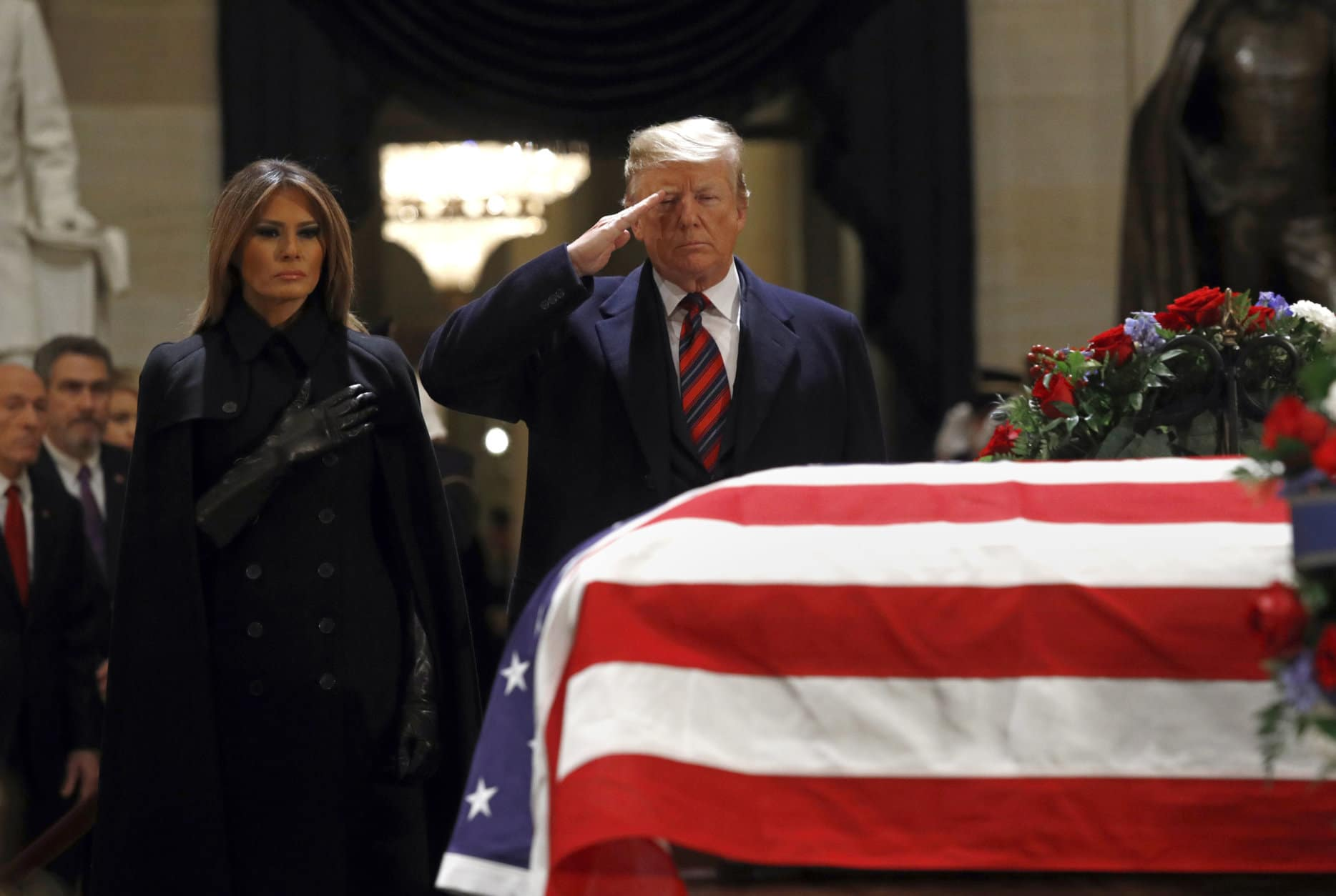 President Donald Trump salutes alongside first lady Melania Trump in front of the flag-draped casket of former President George H.W. Bush in the Capitol Rotunda in Washington, Monday, Dec. 3, 2018. (AP Photo/Patrick Semansky)