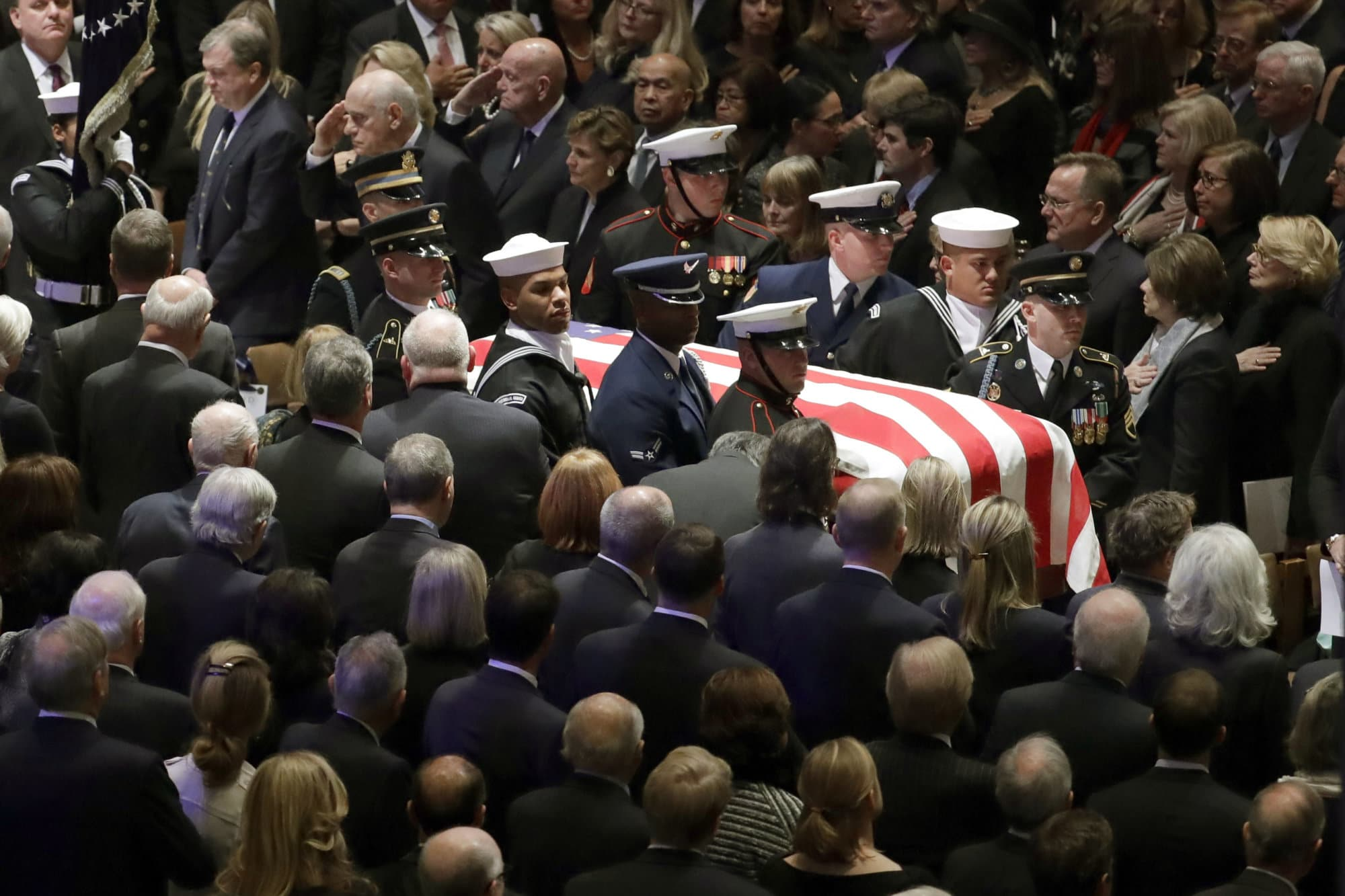 The flag-draped casket of former President George H.W. Bush is carried by a military honor guard during a State Funeral at the National Cathedral, Wednesday, Dec. 5, 2018, in Washington. (AP Photo/Evan Vucci)