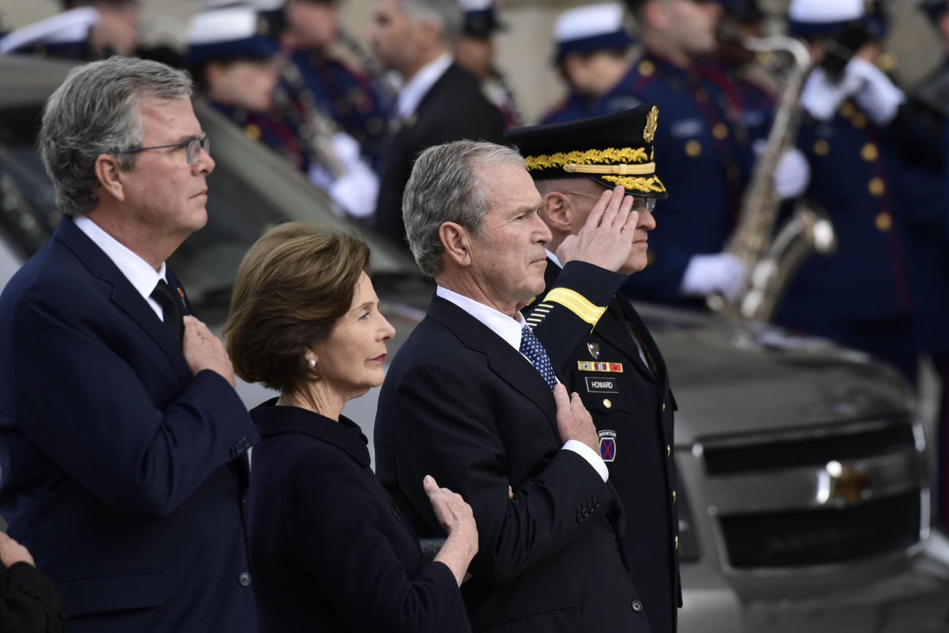 President George W. Bush, his wife Laura Bush and brother Jeb Bush watch as the casket of former President George H.W. Bush arrives at the National Cathedral, Wednesday, Dec. 5, 2018, in Washington, for a State Funeral.(AP Photo/Susan Walsh)