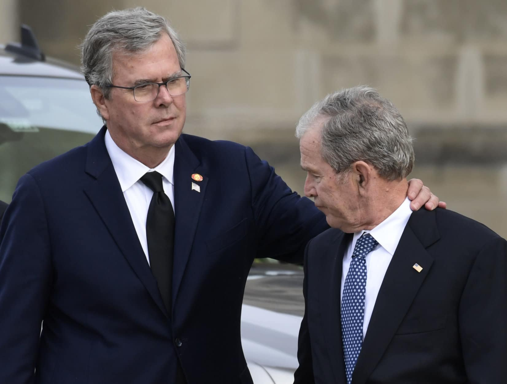 Former Florida Gov. Jeb Bush, left, reaches out to his brother, former President George W. Bush, right, as they arrive to watch the casket of former President George H.W. Bush arrive at the National Cathedral, Wednesday, Dec. 5, 2018, in Washington, for a State Funeral. (AP Photo/Susan Walsh)