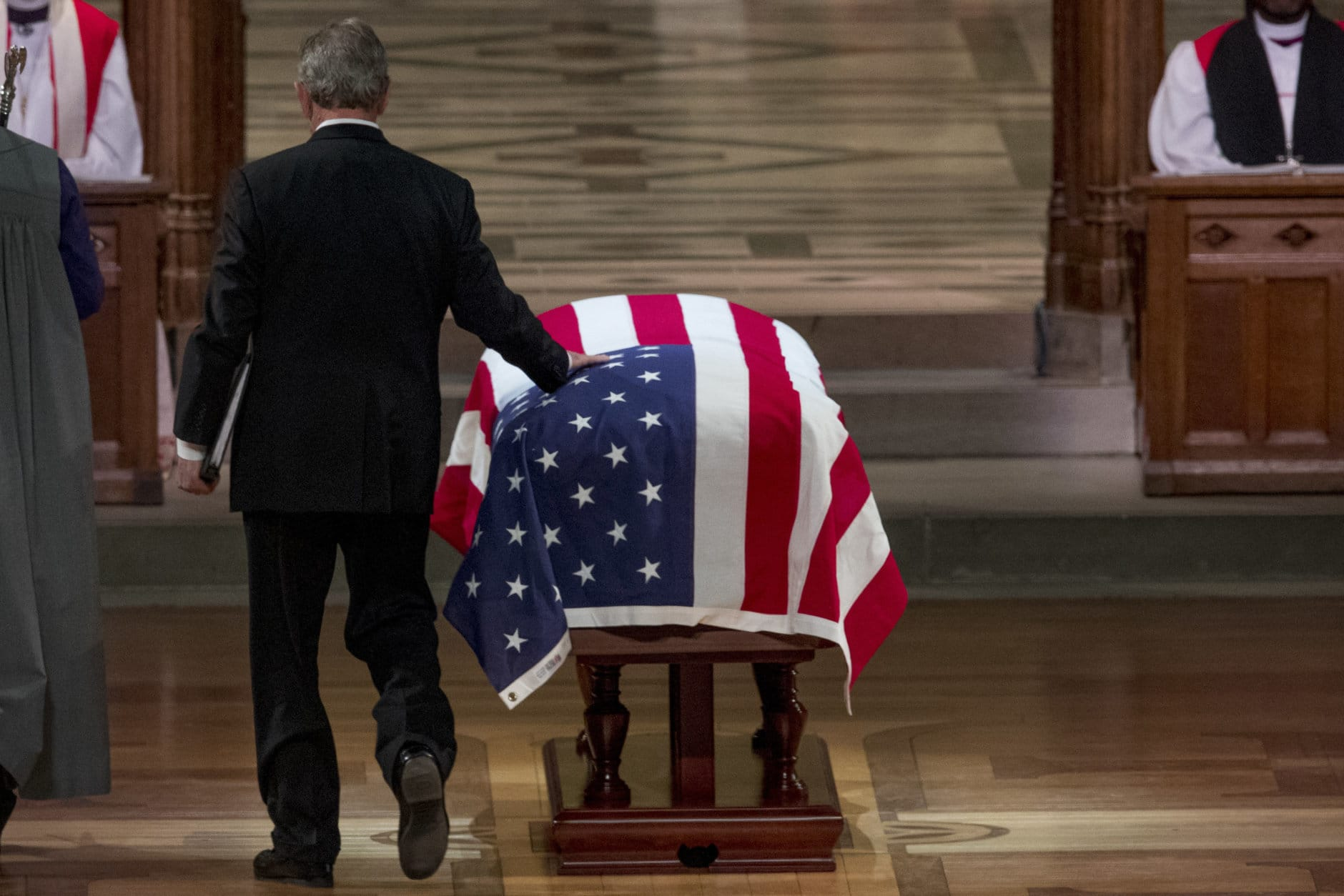 Former President George Bush touches the flag-draped casket of his father, former President George H.W. Bush, as he prepares to speak during his State Funeral at the National Cathedral, Wednesday, Dec. 5, 2018, in Washington. (AP Photo/Andrew Harnik, Pool)