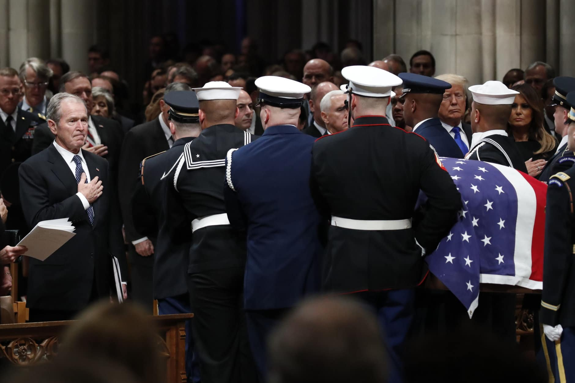 Former President George W. Bush places his hand over his heart as the flag-draped casket of former President George H.W. Bush is carried by a joint services military honor guard after the State Funeral at the National Cathedral, Wednesday, Dec. 5, 2018, in Washington. (AP Photo/Alex Brandon, Pool)