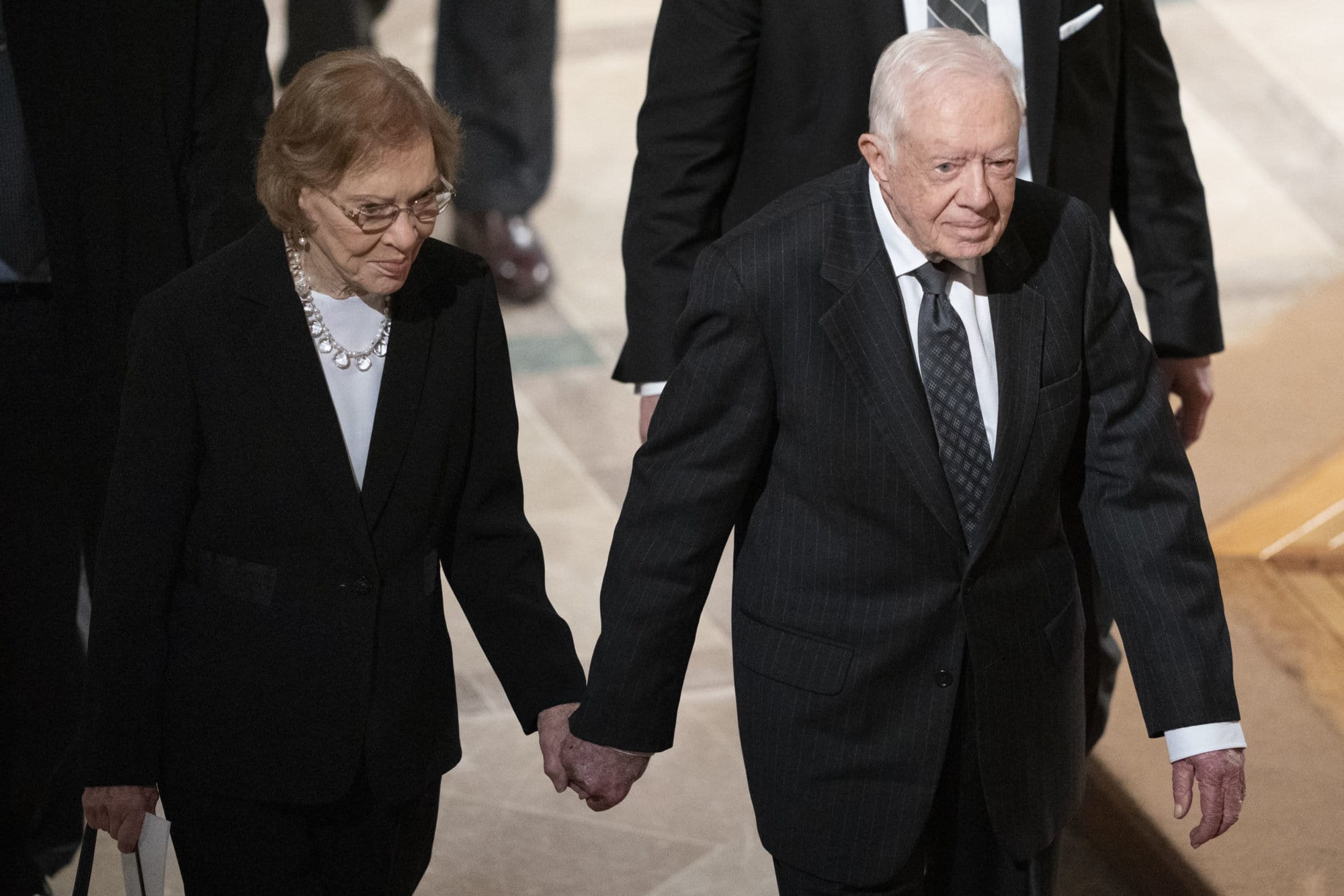 Former President Jimmy Carter, and Rosalynn Carter hold hands as they walk from a State Funeral for former President George H.W. Bush at the National Cathedral, Wednesday, Dec. 5, 2018, in Washington. (AP Photo/Carolyn Kaster)