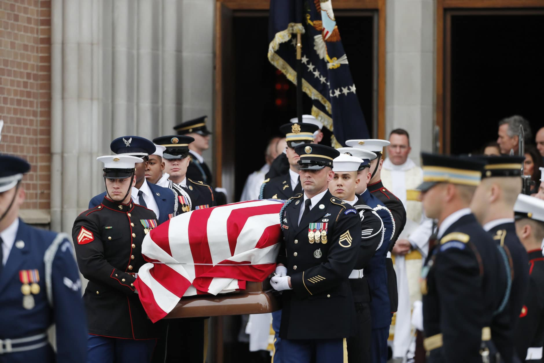 A military honor guard carries the flag-draped casket of former President George H.W. Bush from St. Martin's Episcopal Church following his funeral service Thursday, Dec. 6, 2018, in Houston. (AP Photo/Gerald Herbert)
