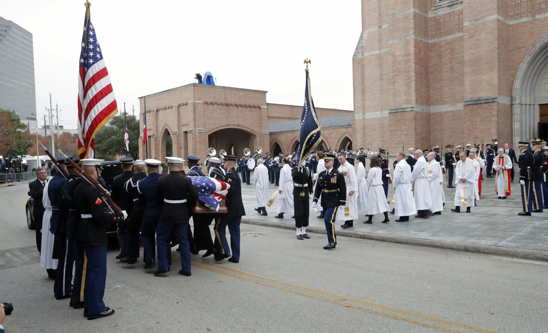 A military honor guard carries the flag-draped casket of former President George H.W. Bush to a hearse following his funeral service at St. Martin's Episcopal Church Thursday, Dec. 6, 2018, in Houston. (AP Photo/Gerald Herbert)