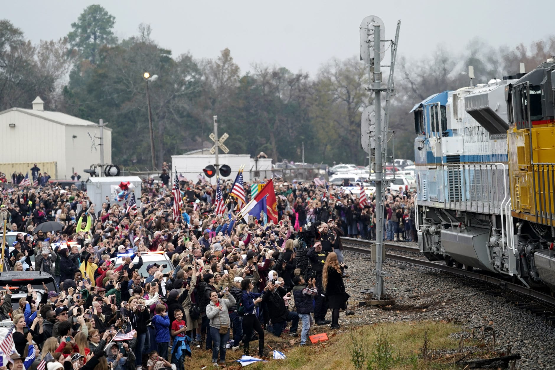 People pay their respects as the train carrying the casket of former President George H.W. Bush passes Thursday, Dec. 6, 2018, along the route from Spring to College Station, Texas. (AP Photo/David J. Phillip, Pool)