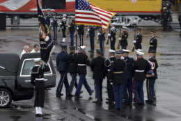 The flag-draped casket of former President George H.W. Bush is carried by a joint services military honor guard from a hearse at Union Pacific Westfield auto facility Thursday, Dec. 6, 2018, in Spring, Texas. (AP Photo/Kiichiro Sato)