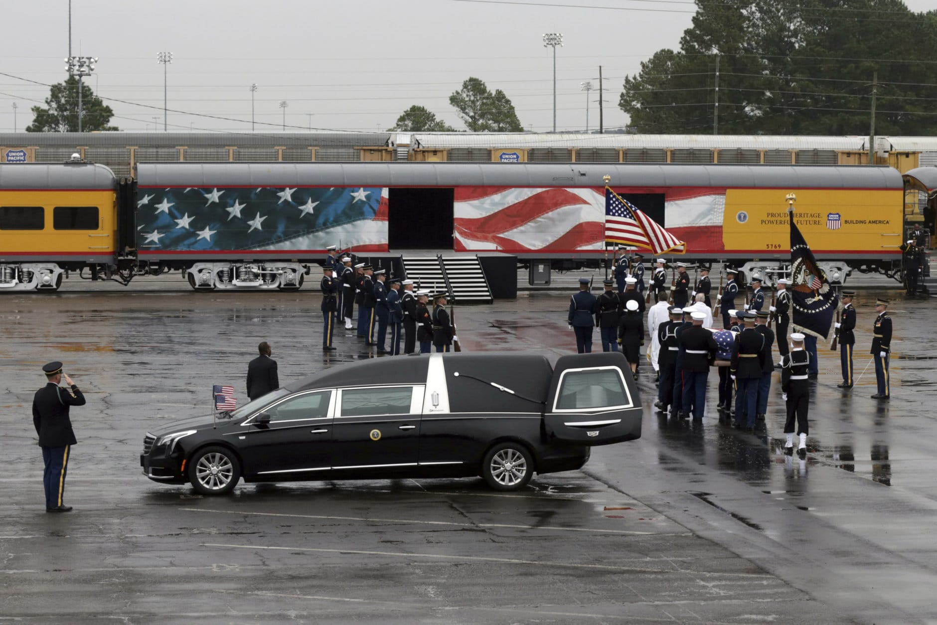 The flag-draped casket of former President George H.W. Bush is carried by a joint services military honor guard to a train at Union Pacific Westfield auto facility Thursday, Dec. 6, 2018, in Spring, Texas. (AP Photo/Kiichiro Sato)