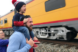 Ryder Davis, 3, watches the memorial train for President George H.W. Bush pass through Pinehurst, Texas, atop the shoulders of his father, 27-year-old Matthew Davis, on Thursday, in Pinehurst, Texas. On Thursday, that same 4,300-horsepower machine left a suburban Houston railyard loaded with Bush's casket for his final journey after almost a week of ceremonies in Washington and Texas. (AP Photo/Nomaan Merchant)