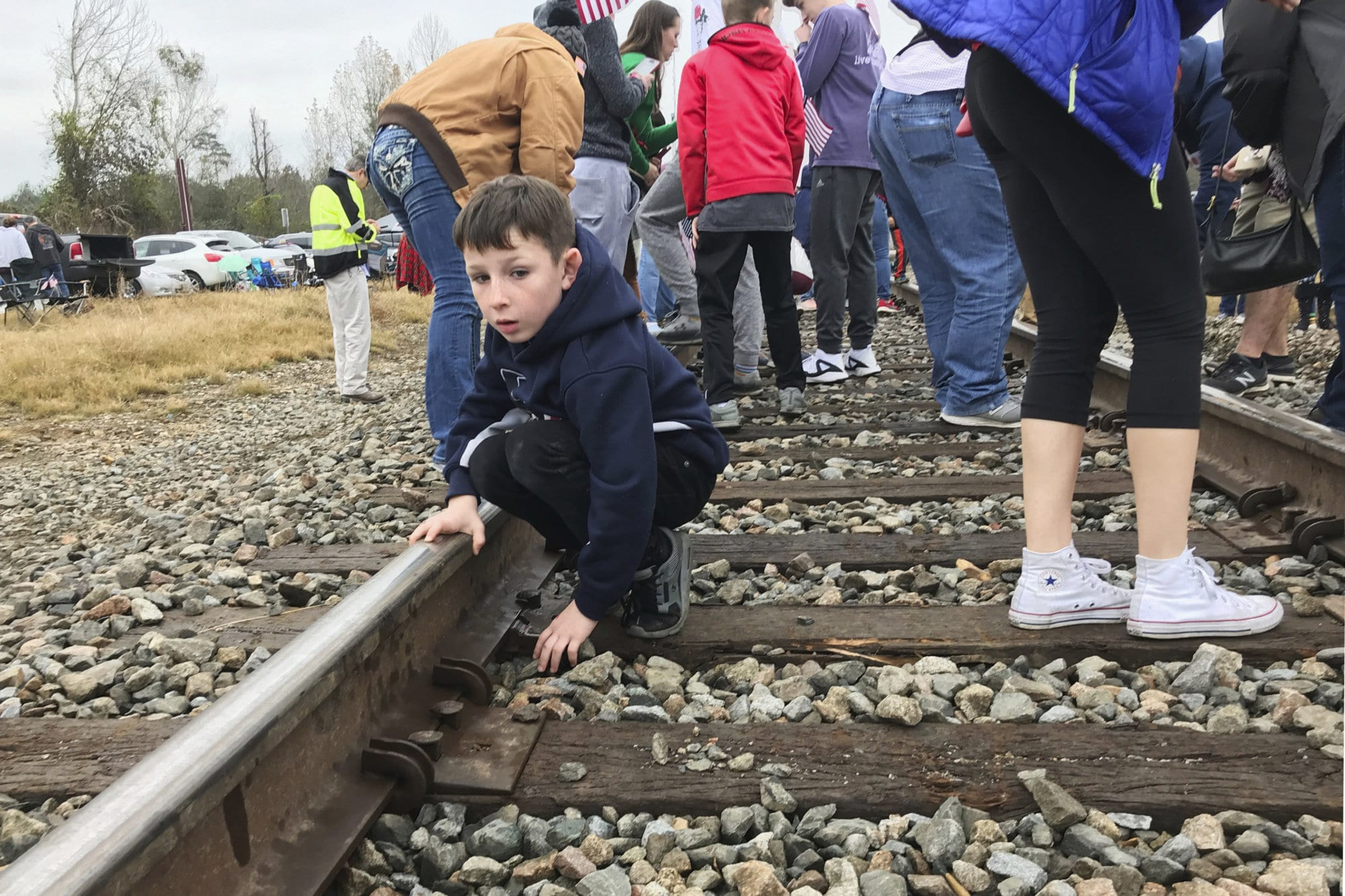Steven Lowry, 7, picks through the rocks underneath the train tracks moments after the memorial train for President George H.W. Bush had passed through Pinehurst, Texas, on Thursday, Dec. 6, 2018. Many people who watched the train pass by took rocks or coins that were flattened by the train as keepsakes. (AP Photo/Nomaan Merchant)
