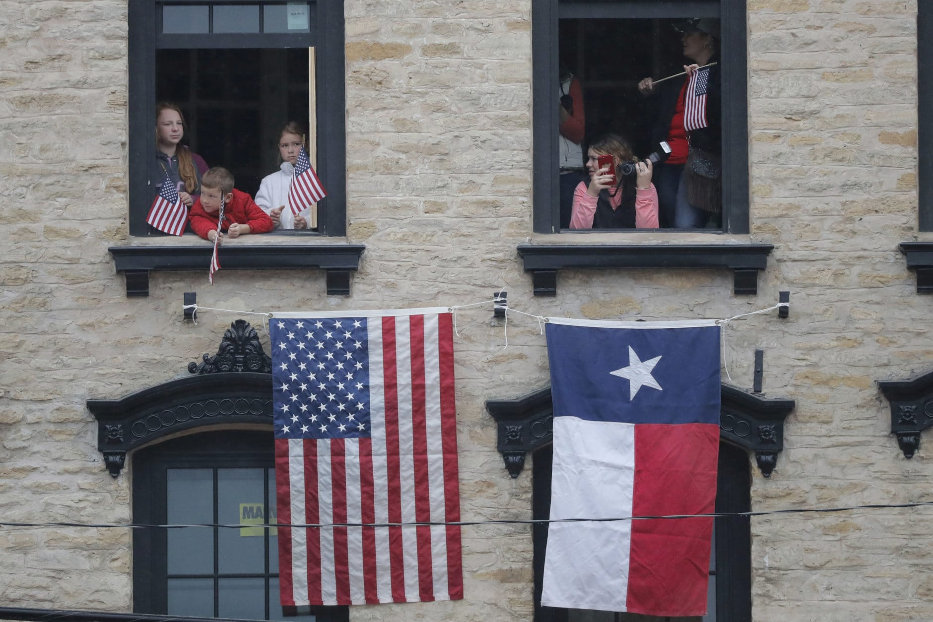 People look from a building as they pay their respects as the train carrying the casket of former President George H.W. Bush passes through Navasota, Texas Thursday, Dec. 6, 2018. (AP Photo/Gerald Herbert)