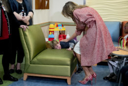First lady Melania Trump, greets a shy boy who was released from the neonatal intensive care unit (NICU) at Children's National Health System, Thursday, Dec. 13, 2018, in Washington. (AP Photo/Andrew Harnik)