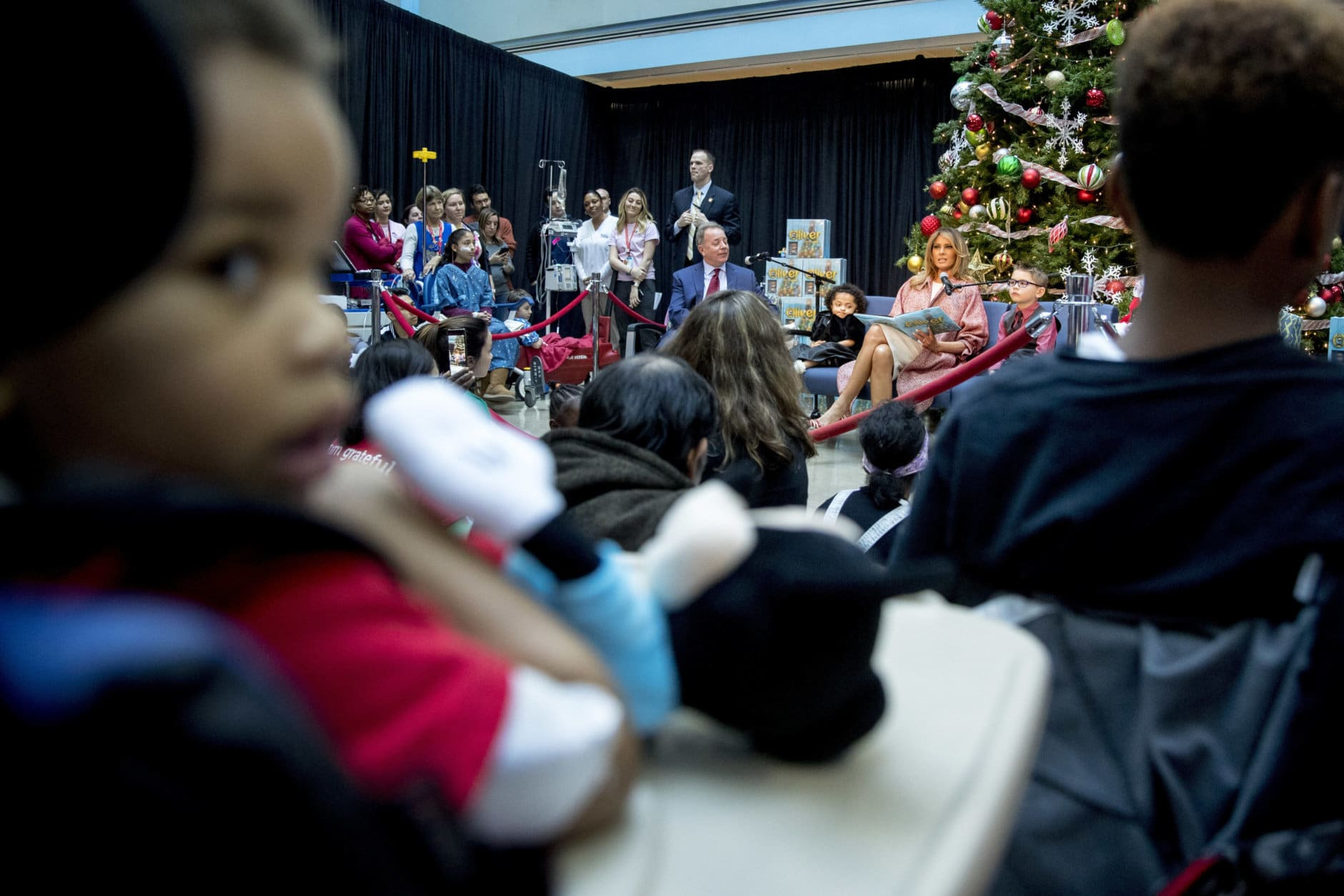 """First lady Melania Trump reads """"Oliver the Ornament"""" to children at Children's National Health System, Thursday, Dec. 13, 2018, in Washington. Also present is the author of the book, Todd Zimmermann, center. (AP Photo/Andrew Harnik)"""