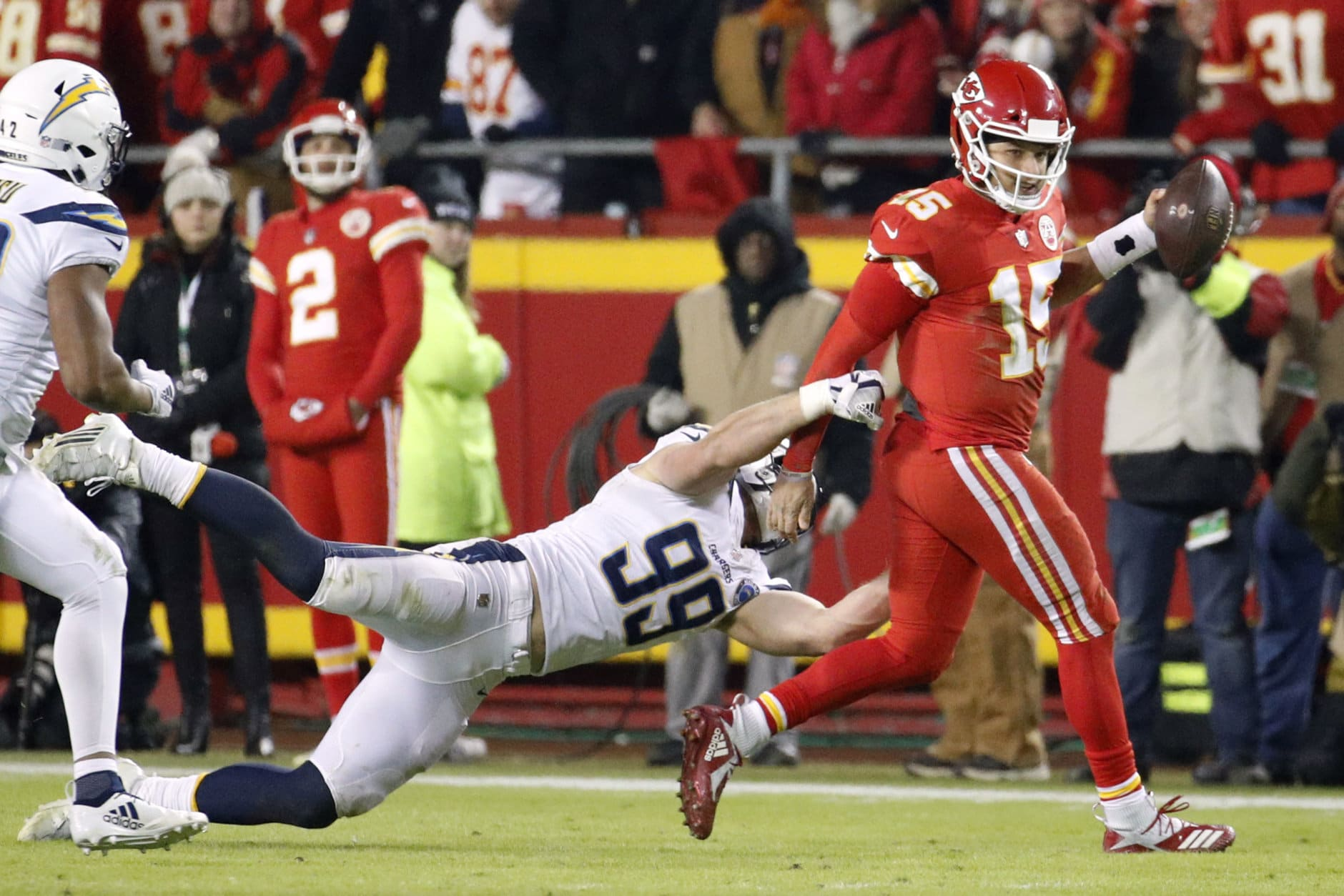 Kansas City Chiefs quarterback Patrick Mahomes (15) runs past a tackle attempt by Los Angeles Chargers defensive end Joey Bosa (99) during the second half of an NFL football game in Kansas City, Mo., Thursday, Dec. 13, 2018. (AP Photo/Charlie Riedel)