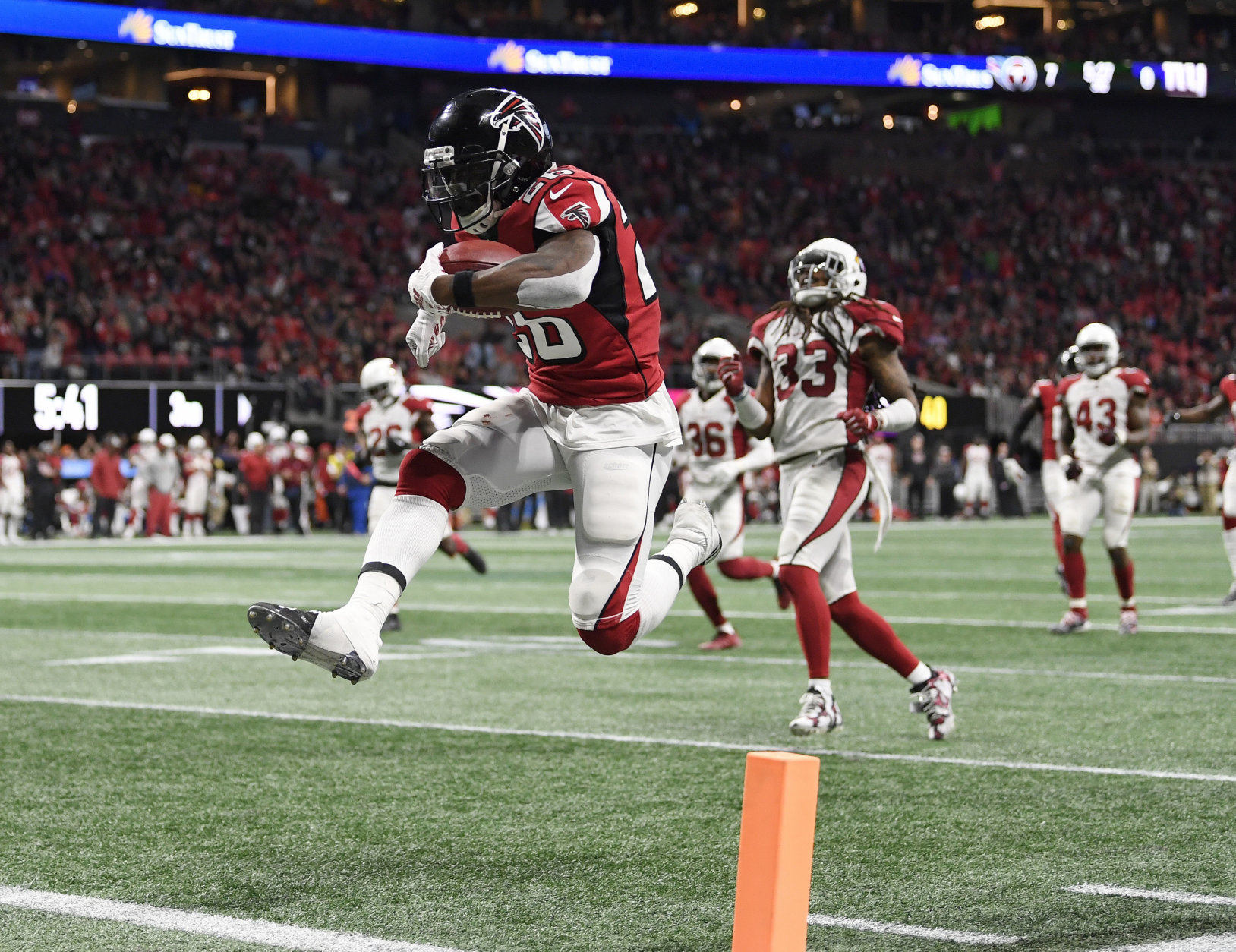 Atlanta Falcons running back Tevin Coleman (26) leaps into the end zone as he scores on a pass from Matt Ryan during the second half of an NFL football game against the Arizona Cardinals, Sunday, Dec. 16, 2018, in Atlanta. (AP Photo/Danny Karnik)