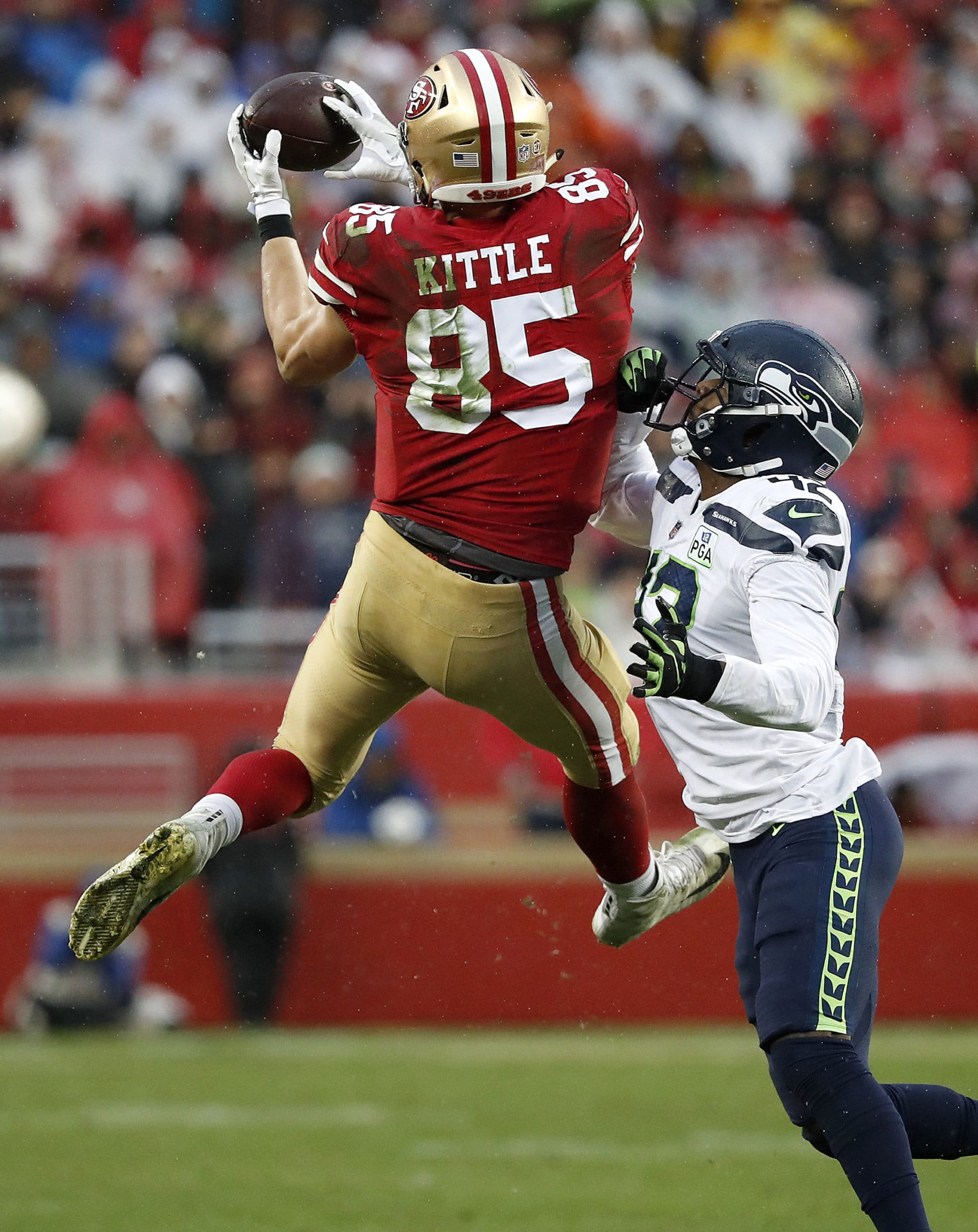 San Francisco 49ers tight end George Kittle (85) catches a pass over Seattle Seahawks defensive back Delano Hill during the second half of an NFL football game in Santa Clara, Calif., Sunday, Dec. 16, 2018. (AP Photo/Tony Avelar)