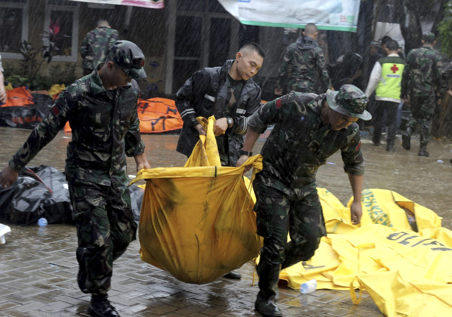 Indonesian soldiers carry a body bag containing the body of a tsunami victim, in Carita, Indonesia, Sunday, Dec. 23, 2018. The tsunami occurred after the eruption of a volcano around Indonesia's Sunda Strait during a busy holiday weekend, sending water crashing ashore and sweeping away hotels, hundreds of houses and people attending a beach concert. (AP Photo)