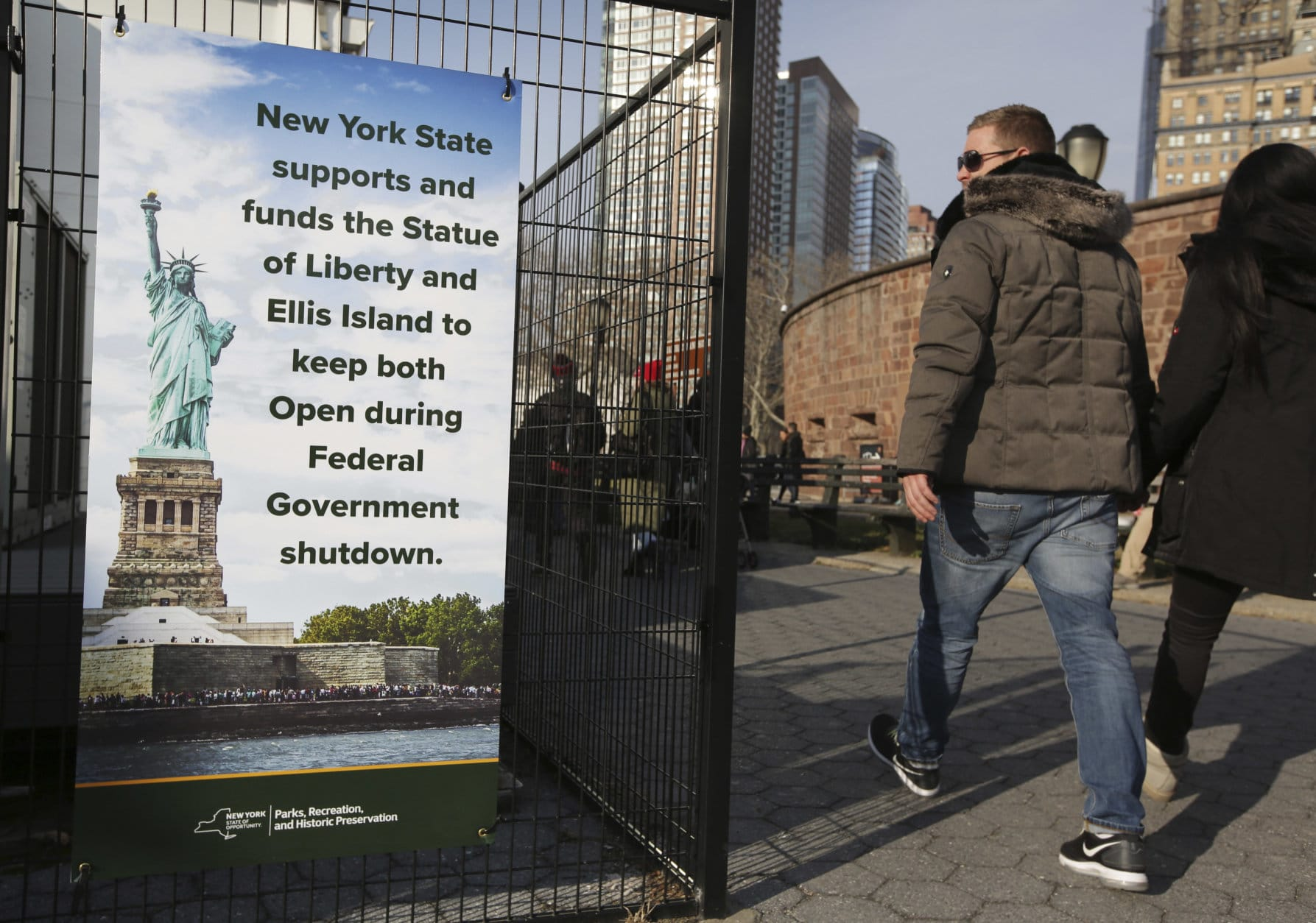 Tourists walk past a sign near the embarkation point for the Statue of Liberty in New York, Thursday, Dec. 27, 2018. The Statue of Liberty and Ellis Island will remain open despite the ongoing partial government shutdown, even as some national parks and monuments close down, according to New York Gov. Andrew Cuomo. (AP Photo/Seth Wenig)