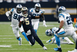 New Orleans Saints quarterback Teddy Bridgewater (5) goes to slide on a carry between Carolina Panthers strong safety Eric Reid (25) and defensive end Bryan Cox (91) in the first half of an NFL football game in New Orleans, Sunday, Dec. 30, 2018. (AP Photo/Butch Dill)