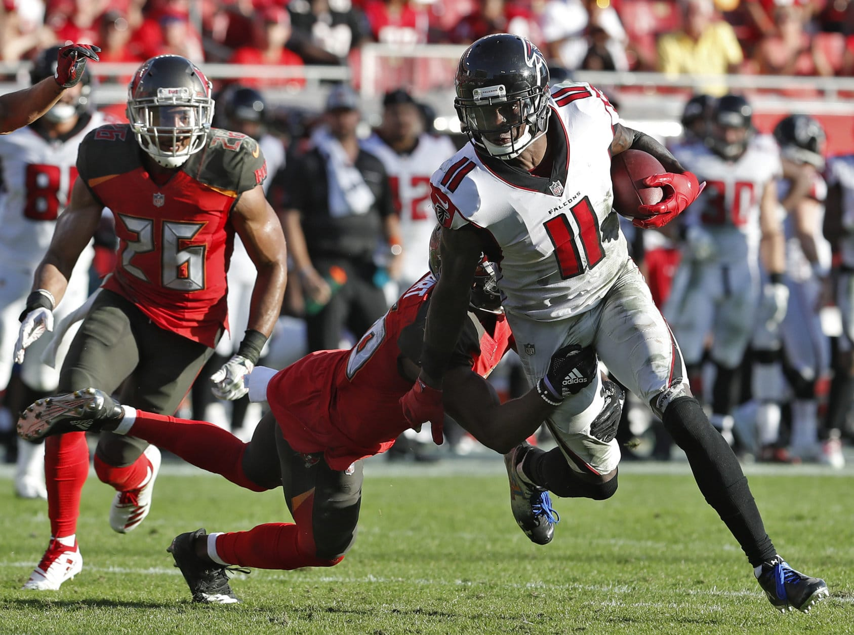 Atlanta Falcons wide receiver Julio Jones (11) is stopped by Tampa Bay Buccaneers cornerback M.J. Stewart (36) and defensive back Andrew Adams (26) after a reception during the second half of an NFL football game Sunday, Dec. 30, 2018, in Tampa, Fla. (AP Photo/Mark LoMoglio)