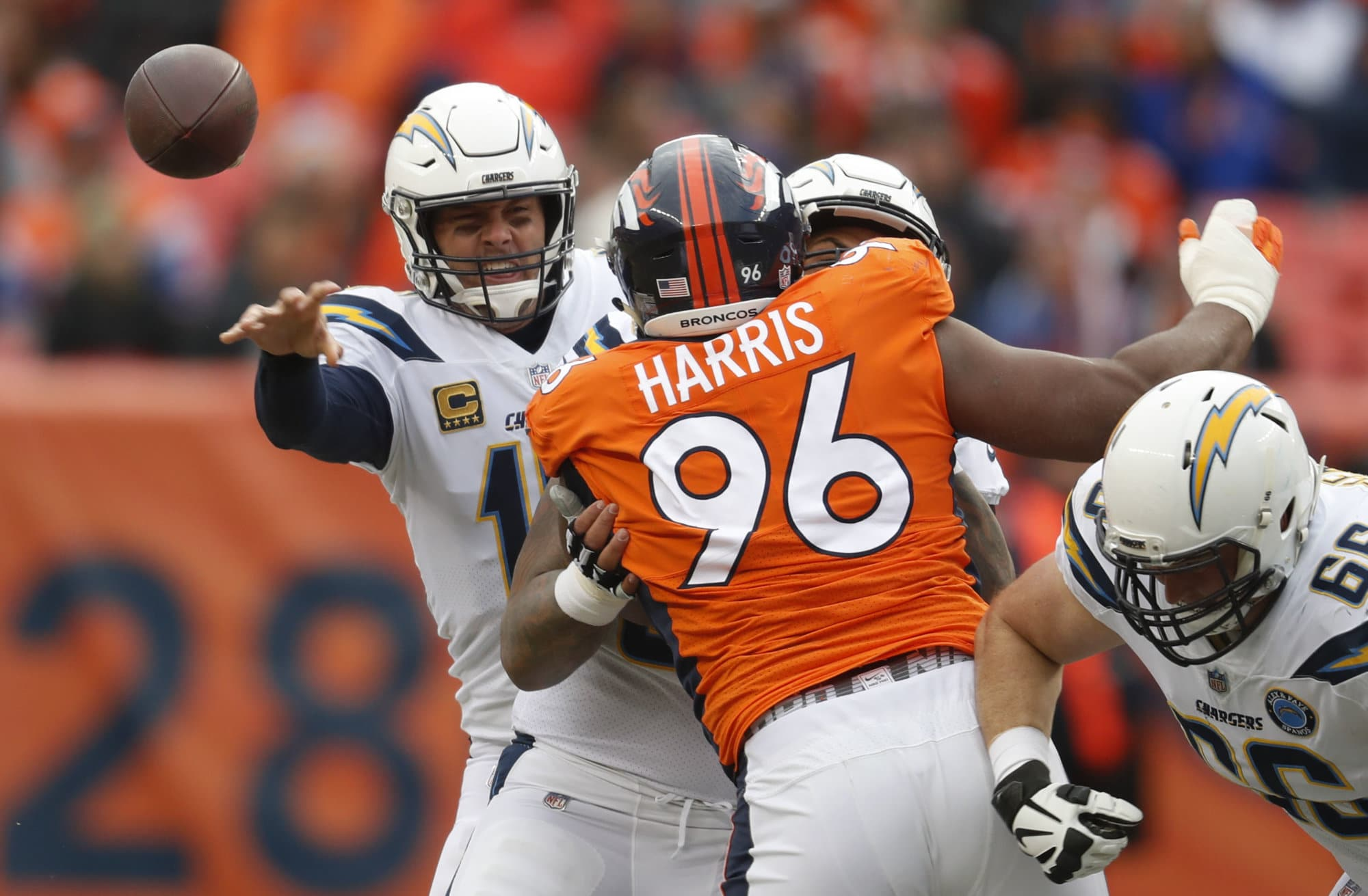 Los Angeles Chargers quarterback Philip Rivers, left, throws a pass under pressure from Denver Broncos defensive end Shelby Harris (96) during the first half of an NFL football game, Sunday, Dec. 30, 2018, in Denver. (AP Photo/David Zalubowski)