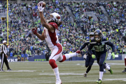 Arizona Cardinals' Larry Fitzgerald, left, snags a one-handed touchdown pass against the Seattle Seahawks during the first half of an NFL football game, Sunday, Dec. 30, 2018, in Seattle. (AP Photo/John Froschauer)