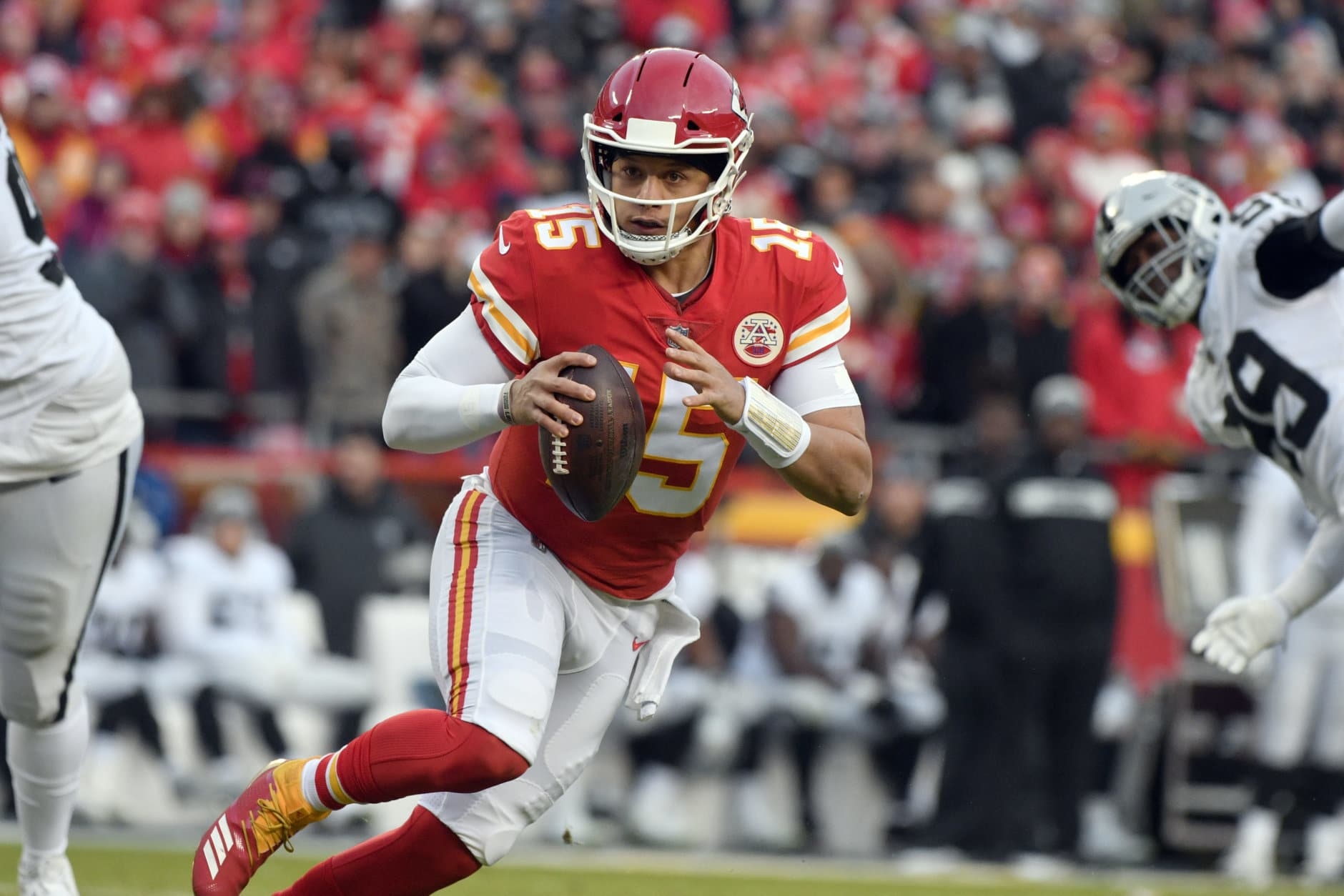 Kansas City Chiefs quarterback Patrick Mahomes (15) scrambles between Oakland Raiders defensive tackle Johnathan Hankins (90) and defensive end Arden Key (99) during the first half of an NFL football game in Kansas City, Mo., Sunday, Dec. 30, 2018. (AP Photo/Ed Zurga)