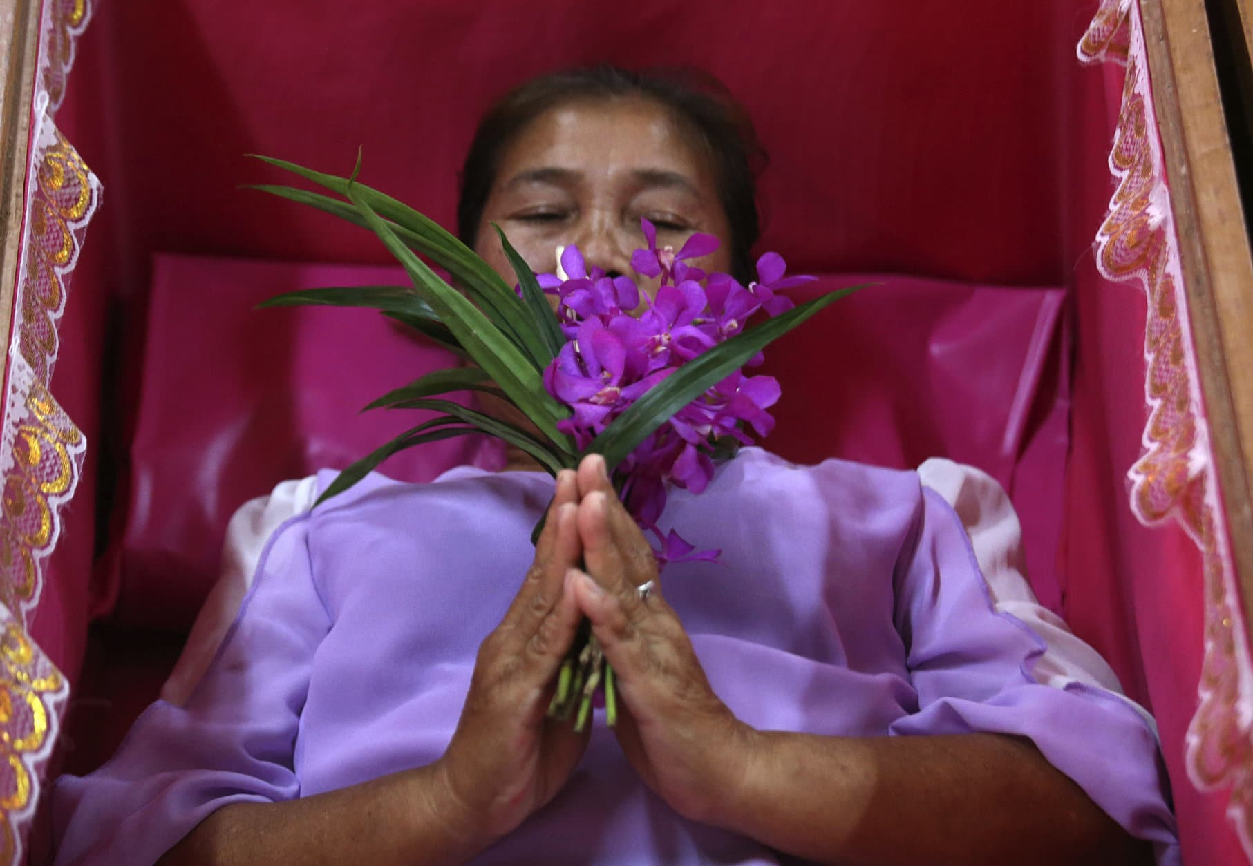 A worshipper prays as she takes her turn lying in a coffin at the Takien temple in suburban Bangkok, Thailand Monday, Dec. 31, 2018. Worshippers believe that the coffin ceremony – symbolizing death and rebirth – helps them rid themselves of bad luck and are born again for a fresh start in the new year. (AP Photo/Sakchai lalit)
