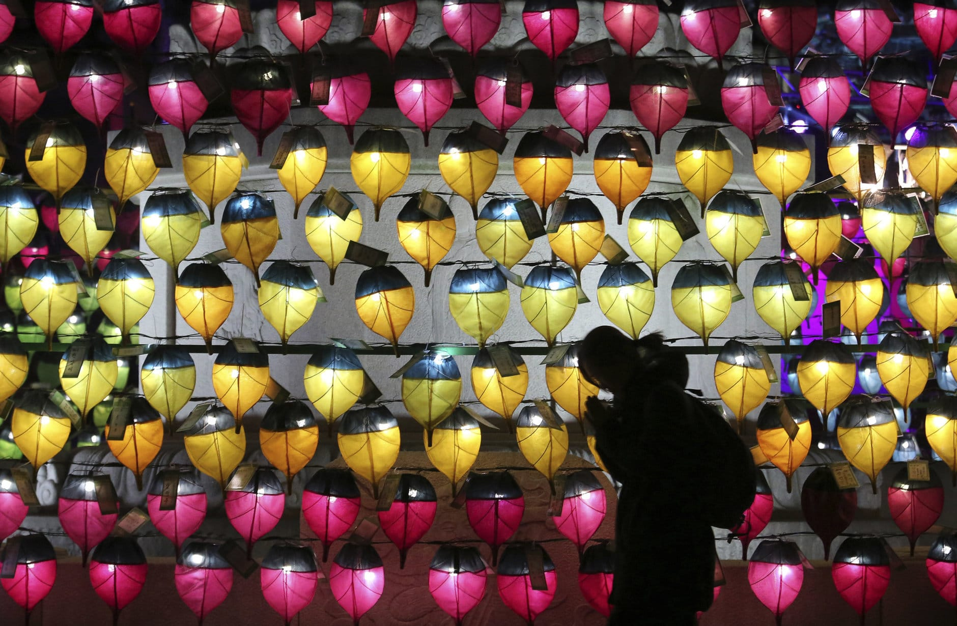 A woman prays in front of a wall of lanterns to celebrate the New Year at the Jogyesa Buddhist temple in Seoul, South Korea, Monday, Dec. 31, 2018. (AP Photo/Ahn Young-joon)