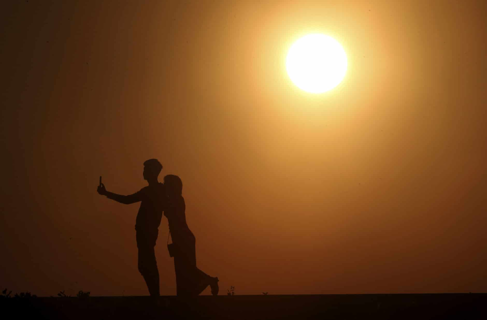 A couple takes a selfie photo during the last sunset of the year in Naypyitaw, Myanmar, Monday, Dec. 31, 2018. (AP Photo/Aung Shine Oo)