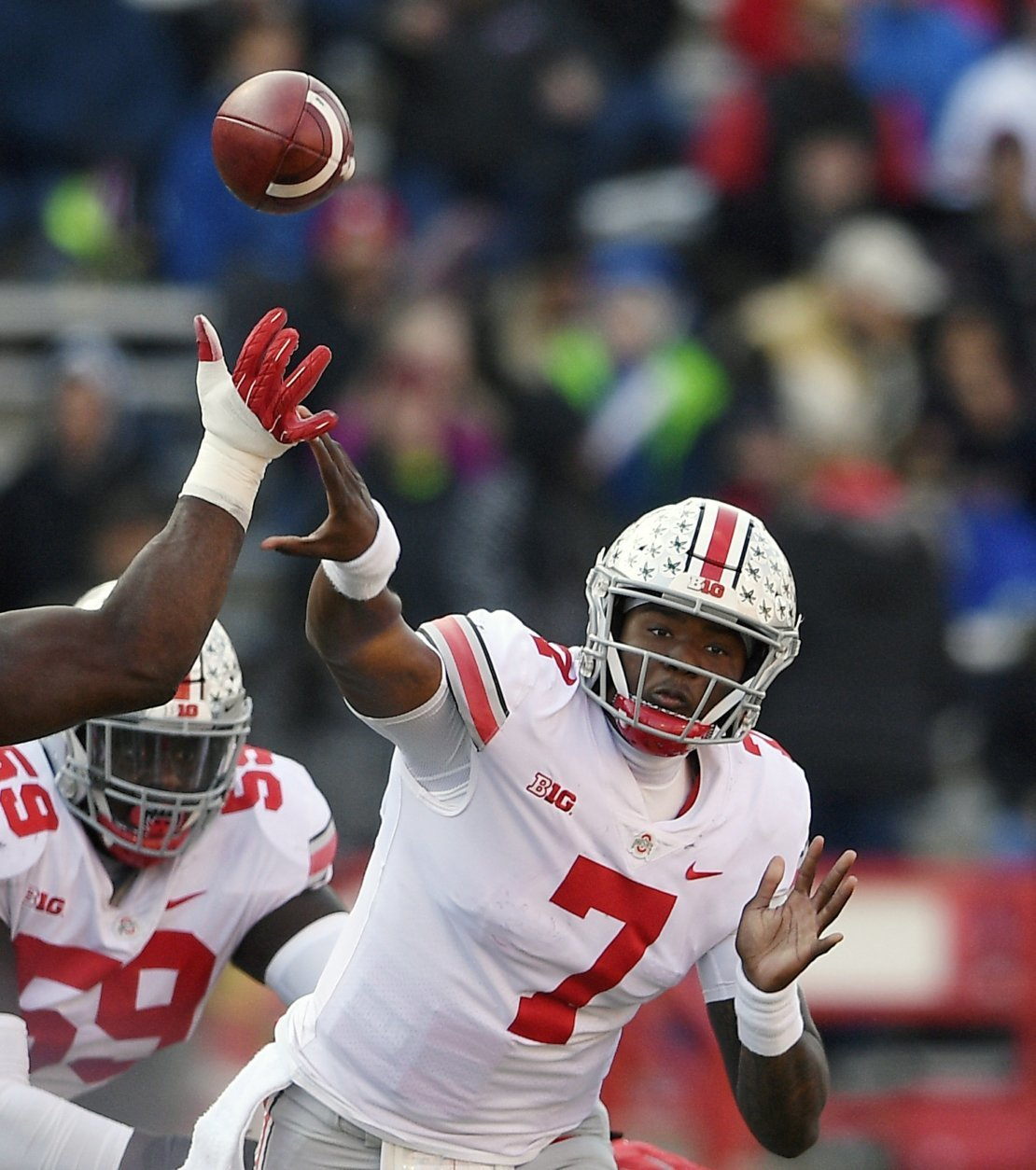 FILE - In this Saturday, Nov. 17, 2018, file photo, Ohio State quarterback Dwayne Haskins Jr. (7) passes under pressure from a Maryland defender during the second half of an NCAA football game in College Park, Md. Haskins was named offensive player of the year when The Associated Press All-Big Ten Conference team was released Wednesday, Dec. 5, 2018. (AP Photo/Nick Wass, File)