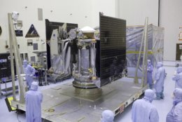 FILE - This May 21, 2016, file photo provided by NASA shows the Osiris-Rex spacecraft inside a servicing facility at Kennedy Space Center in Florida after arriving from Lockheed Martin's facility near Denver. The Osiris-Rex spacecraft entered orbit Monday, Dec. 31, 2018, around the asteroid Bennu, 70 million miles (110 million kilometers) from Earth. It's the smallest celestial body ever to be orbited by a spacecraft. Bennu is just 1,600 feet (500 meters) across. (Dimitri Gerondidakis/NASA via AP, File)