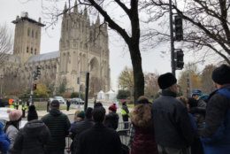 People line Wisconsin Avenue across the street from the Washington National Cathedral as the procession for former President George H.W. Bush approaches. (WTOP/John Aaron)