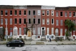 """In this Oct. 26, 2018 photo, a man walks past vacant rowhomes in the Harlem Park neighborhood of Baltimore. """"There are whole sections of our city that look like 1980's Beirut,"""" said Carol Ott, an advocate for tenants' rights in Baltimore who has helped bring the punishing scope of the decades-old problem to light. (AP Photo/Patrick Semansky)"""