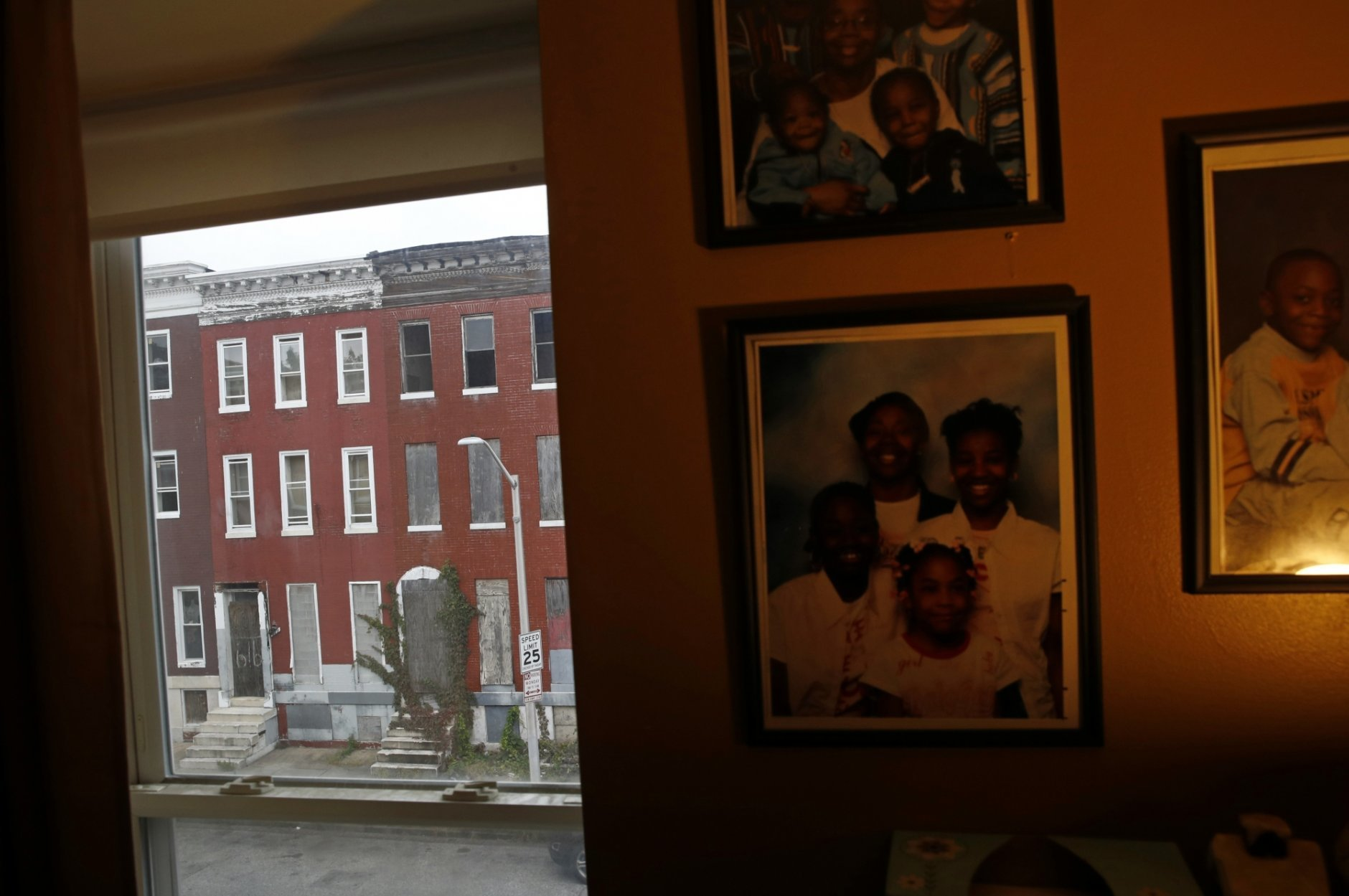 In this Oct. 26, 2018 photo, vacant rowhomes are visible from resident Nayeka Scott's living room in the Harlem Park neighborhood of Baltimore. A sea of roughly 16,000 uninhabitable row homes with weeds growing out of boarded-up windows are symbols of this city's enduring social divide. Housing researchers say some 20,000 other city properties are unoccupied and pose a latent risk of becoming crumbling shells in the future. (AP Photo/Patrick Semansky)