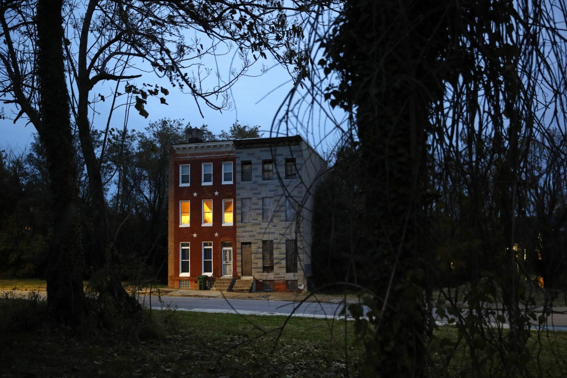 In this Nov. 13, 2018 photo, a pair of rowhomes, one occupied, the other boarded up, stand surrounded by vacant lots at dusk in Baltimore. At a time when rival cities that have grappled with issues of urban decay are gaining residents, Baltimore's decades-long disappearing act is only continuing. It has led all U.S. cities in population loss for the last two years running. (AP Photo/Patrick Semansky)