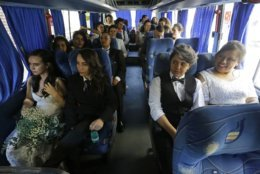 Couples take a bus on their way to a  group marriage of forty same sex couples in Sao Paulo, Brazil, Saturday, Dec. 15, 2018.  With the election of ultra-rightist Jair Bolsonaro as president, hundreds of same sex couples began to marry, fearing that the administration of Bolsonaro, who accumulates a history of homophobic and derogatory comments towards gays, could hinder the union of people of the same sex. (AP Photo/Nelson Antoine)