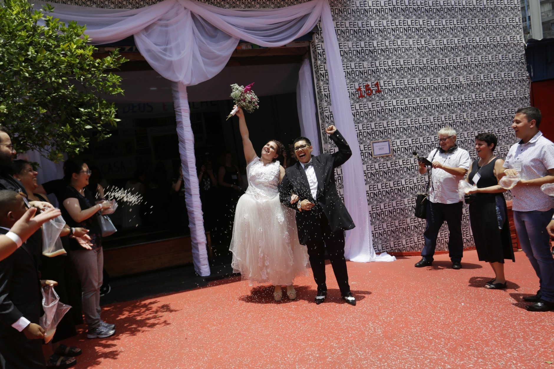 Two women celebrate after getting married in a group marriage of forty same sex couples in Sao Paulo, Brazil, Saturday, Dec. 15, 2018. With the election of ultra-rightist Jair Bolsonaro as president, hundreds of same sex couples began to marry, fearing that the administration of Bolsonaro, who accumulates a history of homophobic and derogatory comments towards gays, could hinder the union of people of the same sex.  (AP Photo/Nelson Antoine)