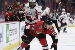 Washington Capitals right wing Devante Smith-Pelly (25) and Ottawa Senators defenseman Maxime Lajoie (58) battle for the puck during the first period of an NHL hockey game, Saturday, Dec. 29, 2018 in Ottawa, Ontario. (Justin Tang/The Canadian Press via AP)