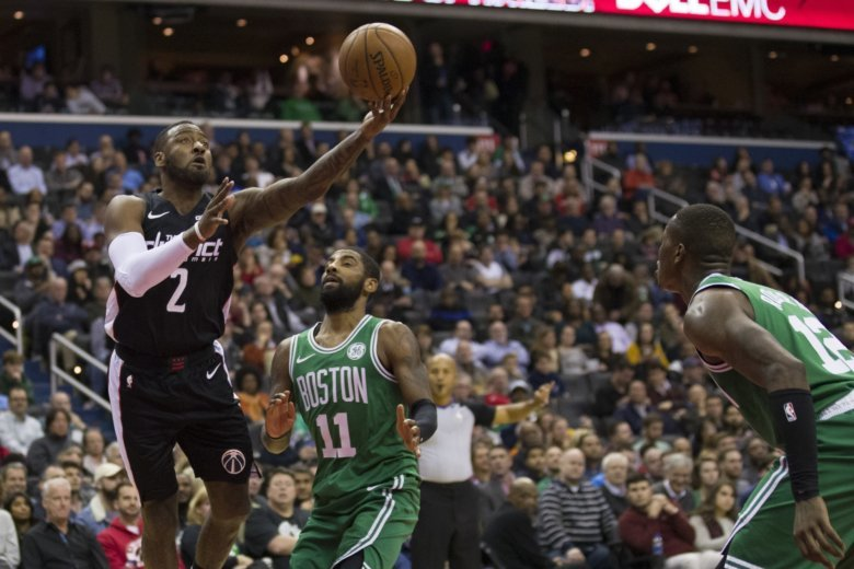 1a1940b667f4 Washington Wizards guard John Wall (2) shoots in front of Boston Celtics  guards Kyrie Irving (11) and Terry Rozier (12) during the first half of an  NBA.