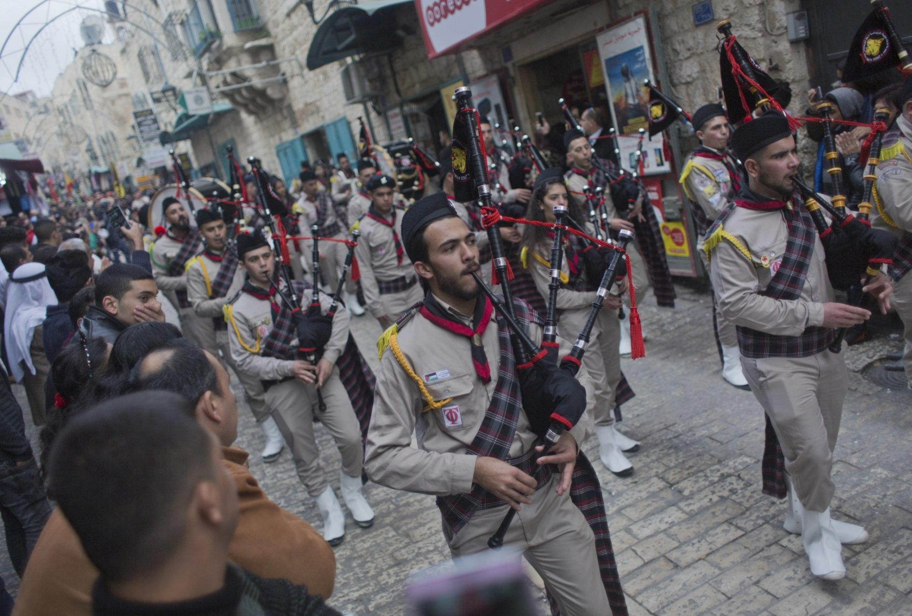 Palestinian scouts march through town ahead of midnight Mass at the Church of the Nativity, traditionally recognized by Christians to be the birthplace of Jesus Christ, in the West Bank city of Bethlehem, Monday, Dec. 24, 2018. Palestinians are preparing to host pilgrims from around the world in celebrating Christmas in the West Bank city of Bethlehem. (AP Photo/Nasser Nasser)